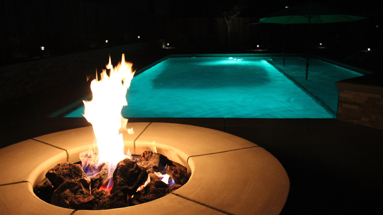 Flaming gas fire pit with glowing pool lighting for nighttime fun.