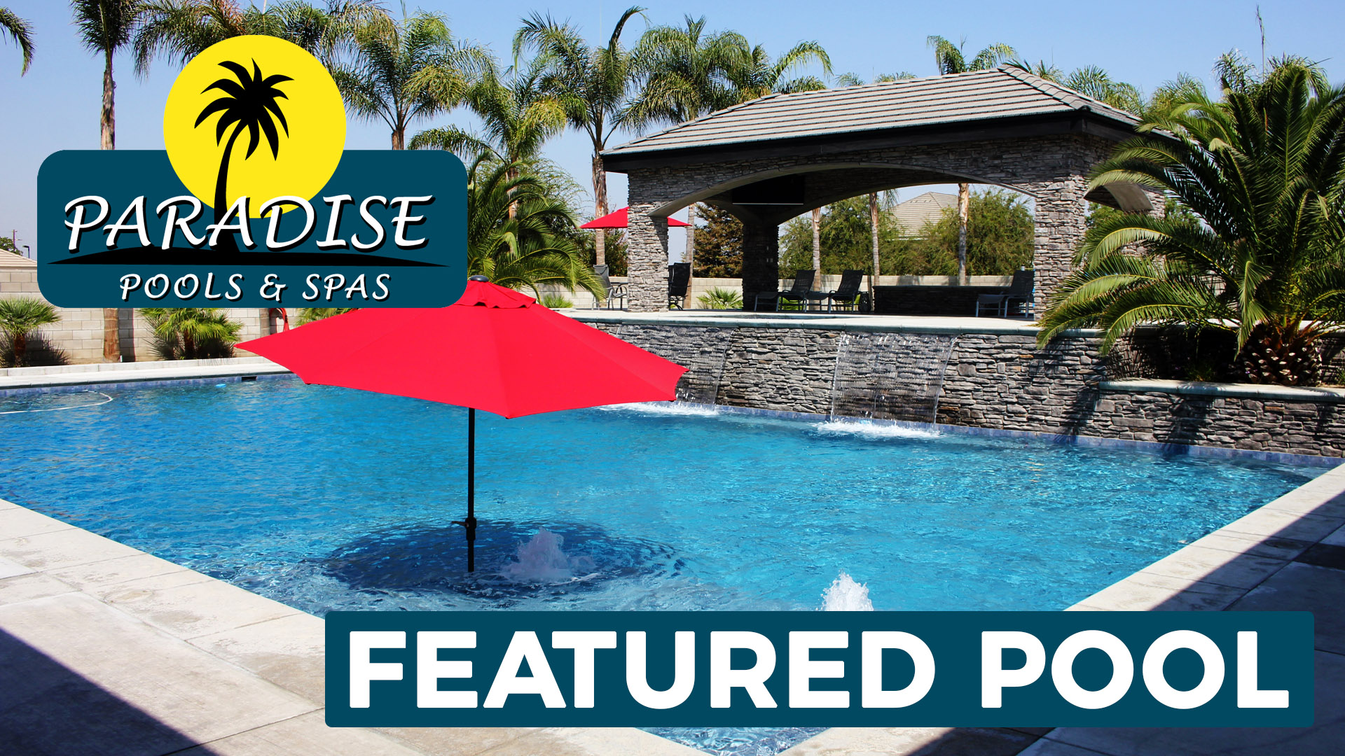 Massive, deep swimming pool with water features, spa and red umbrellas built by Paradise Pools & Spas.