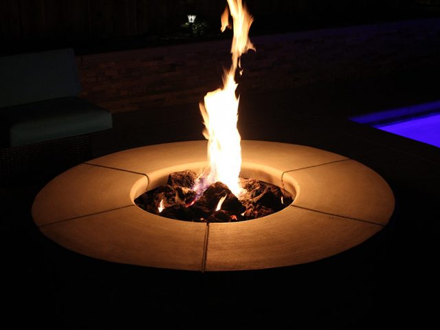 Flaming fire pit by pool in Bakersfield, CA.