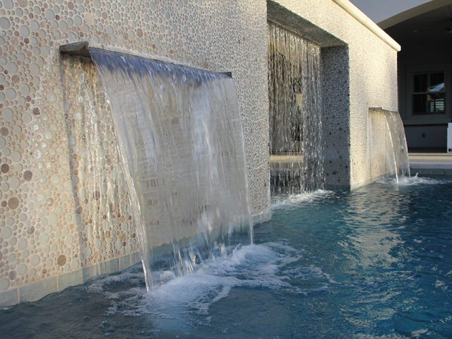 Water wall with two scuppers and a rain curtain pouring into a beautiful pool in Bakersfield, CA.