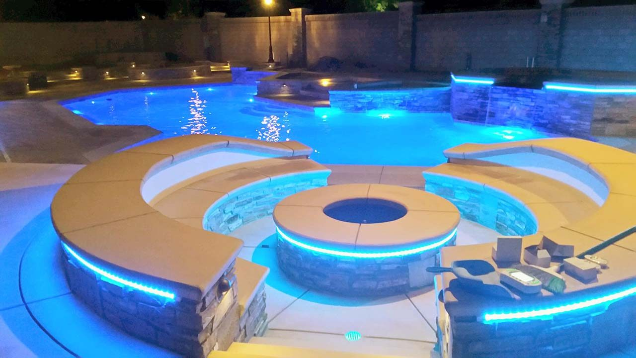 Firepit, pool, spa and water features in the glow of custom lighting by Paradise Pools & Spas.